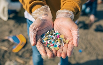 Gloved hands holding a pile of microplastics at the beach